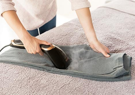 Steam&Go Handheld steamer being used on pants horizontally