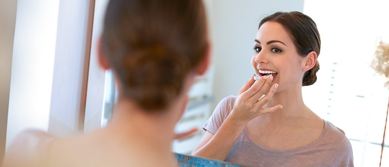 Lady using teeth whitening kit at home