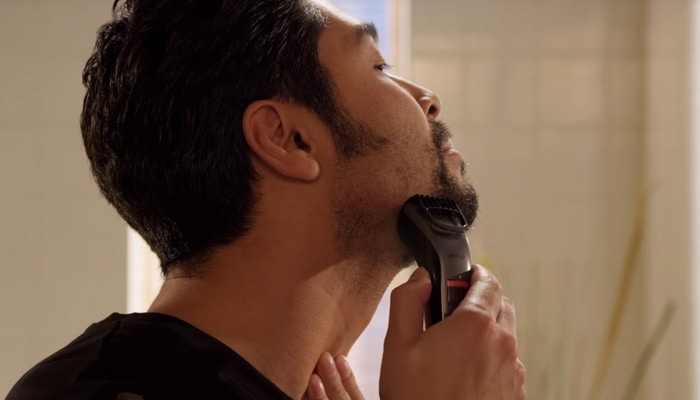 Man trimming his stubble beard with a beard trimmer