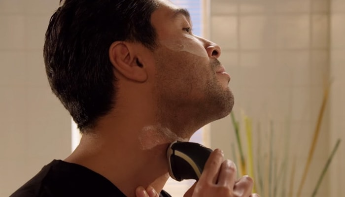 Man shaving his beard neckline to create a stubble beard